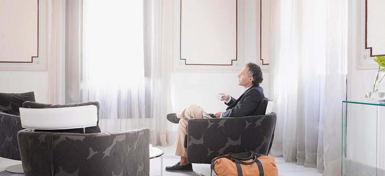 man enjoying espresso in modern hotel suite