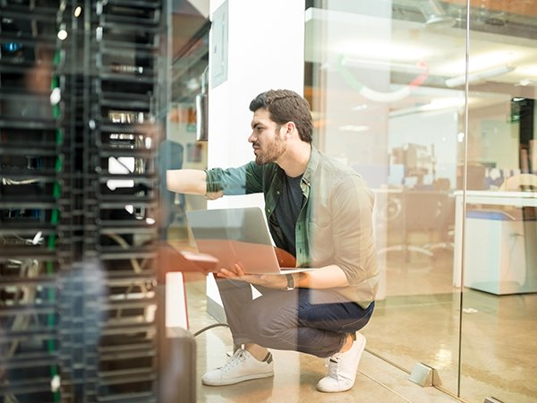 Network administrator with notebook computer sitting in data center room and working with networking device on rack cabinet