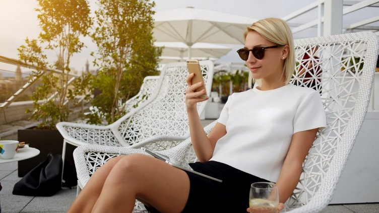 Beautiful woman in sunglasses dressed in fashionable expensive clothes is reading text message on mobile phone, while is sitting with digital tablet on hotel balcony during her business trip abroad; Shutterstock ID 488616601; Departmental Cost Code : 162800; Project Code: GBLMKT; PO Number: GBLMKT; Other: