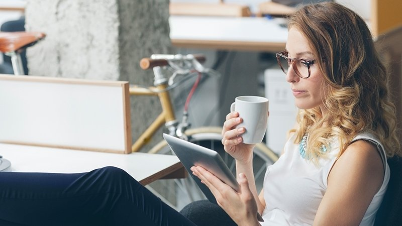 relaxed employee on a tablet drinking coffee