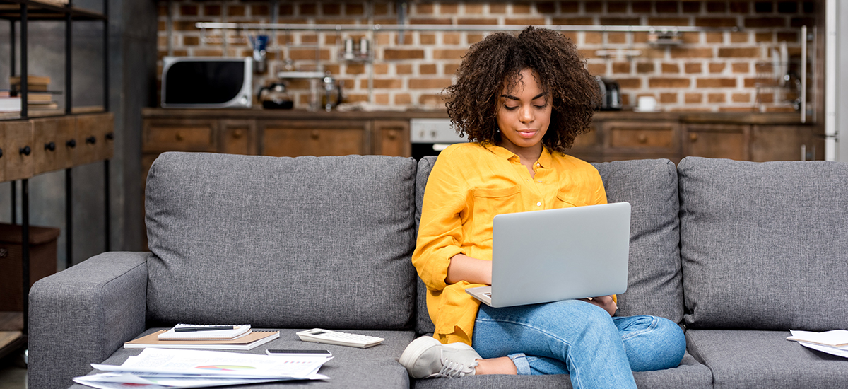 woman sits on couch while remote working