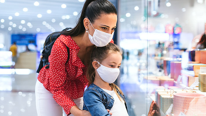 Mother and daughter with face mask standing indoors in shopping center, coronavirus concept.